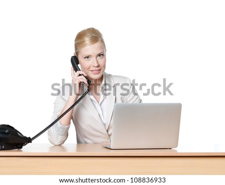 Young business woman sitting at a office table and holding phone handset, isolated