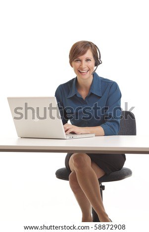 Young business woman sitting at desk with computer and headset