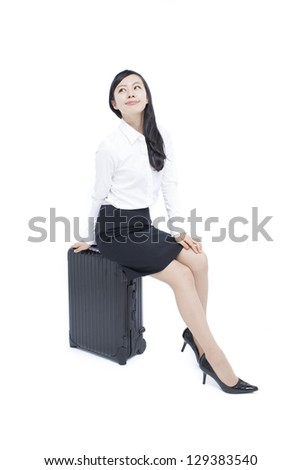 young business woman sitting on suitcase isolated on white background