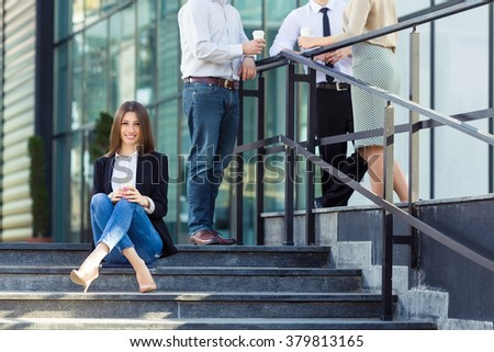Young business woman sitting on the steps in front of the office building with group of her coworkers in the background #379813165