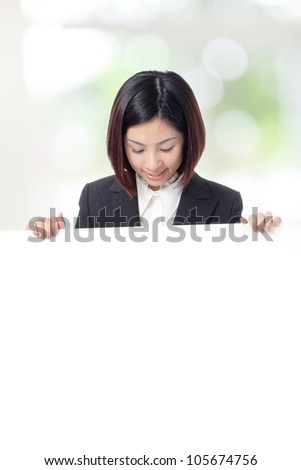 Young Business woman smile look to billboard with empty copy space on green background, model is a asian girl