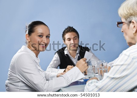 Young business woman smiling and holding a paper in her hands in middle of a meeting with her colleagues - stock photo