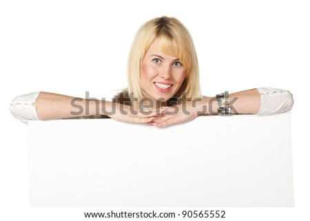 Young business woman standing behind and leaning on a white blank billboard / placard, isolated on white background