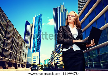 Young business woman standing with laptop in the big city and purposefully looking away.