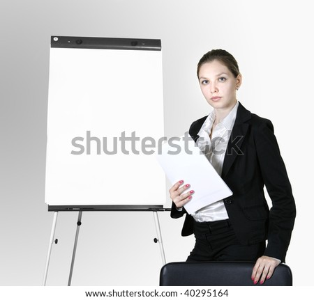 Young business woman stands near flip chart rests in chair