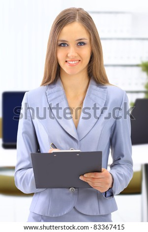 young business woman taking notes on her clipboard