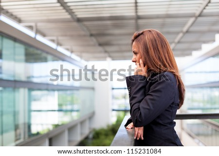 Young business woman talking on cell phone at the office