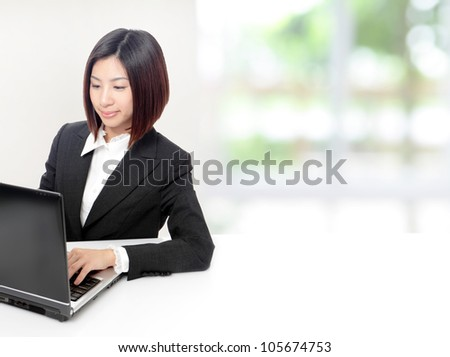 Young Business woman using computer and sit at company office with white table, window outside are green background, model is a asian beauty