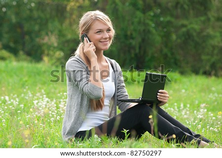 Young  business woman using laptop and talking on a cell phone outdoors