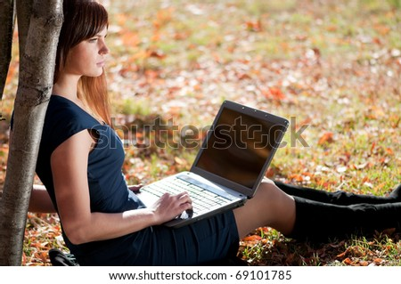 Young business woman using notebook mobile computer at city park. Working student