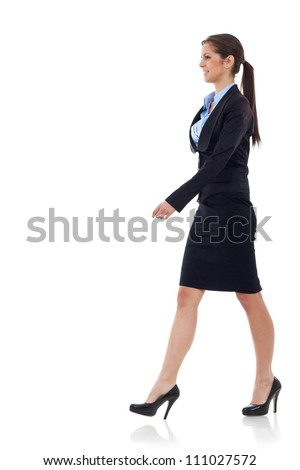 young business woman  walking. She is smiling and looking away from the camera isolated over white background