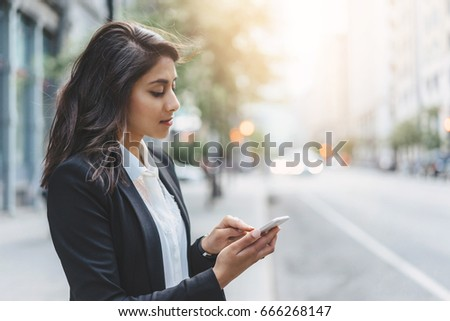 Young business woman wearing black modern suit and using smartphone while coffee break #666268147