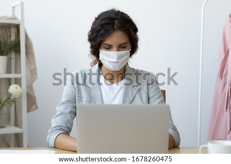Young business woman wearing face mask working on computer seated at workplace desk in office room protecting herself from getting grippe vs COVID-19 corona virus pandemic infectious disease concept