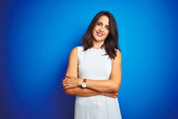 Young business woman wearing white elegant dress standing over blue isolated background happy face smiling with crossed arms looking at the camera. Positive person.