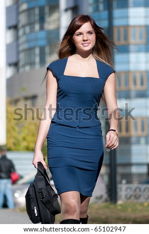 Young business woman with bag go to meeting over blue city. Late. Student