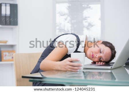 Young business woman with coffee cup resting head on laptop at desk in office