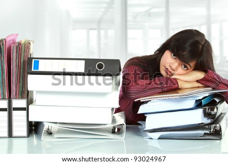 young business woman with many paper work stressed at work