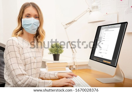 Young business woman working from home, wearing protective mask
