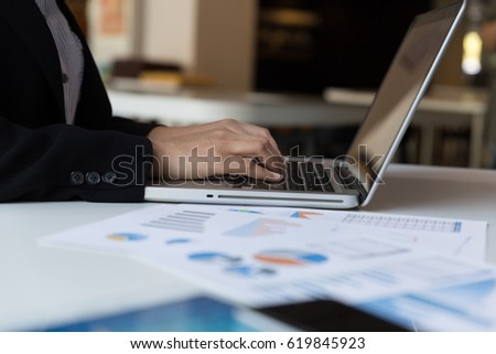 young business woman working in office interior on pc on desk, typing, looking at screen with chart diagrams document. Office person using laptop computer in office workplace