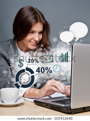 Young business woman working on her laptop. Different icons with functional symbols are flying out of the screen
