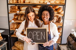 Young business women holding an open sign. Bakery shop female owner showing chalkboard with open sign while opening store. Local business, hospitality, open after lockdown concept.