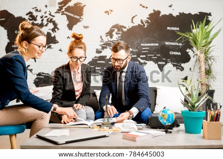 Young businesscouple choosing a trip with agent sitting at the travel agency office with world map on the background ストックフォト ©