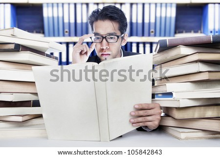 Young businessman analyzing business books at office