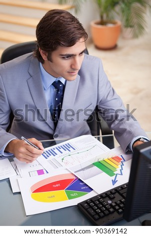 Young businessman analyzing statistics at his desk