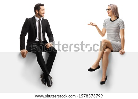 Young businessman and a young lady having a conversation while sitting on a panel isolated on white background