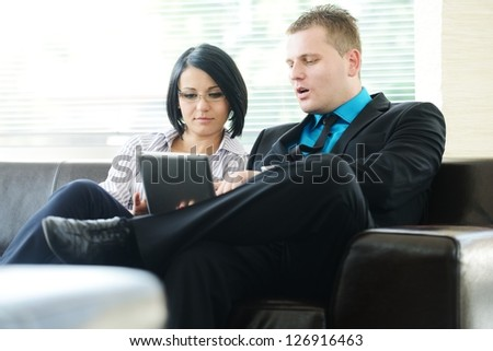 Young businessman and business woman sitting at office lobby on leather sofa working with tablet pc
