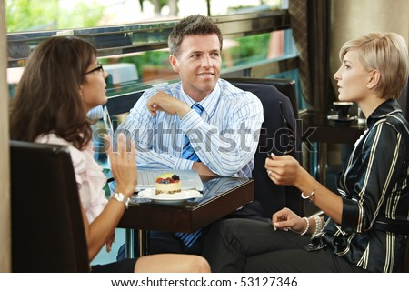 Young businessman and businesswomenhaving a meeting in cafe.