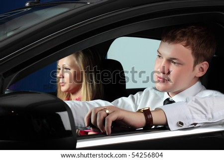 young businessman and charming woman in the car