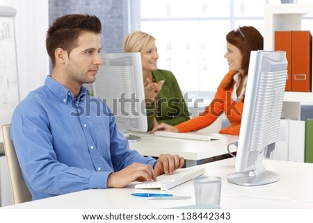 Young businessman and colleagues working in office, sitting at desk, using desktop computer.