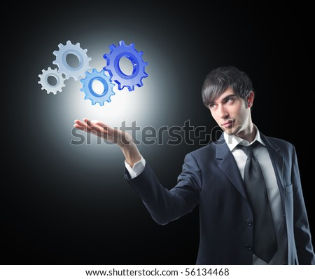 young businessman and 3d gears on dark background