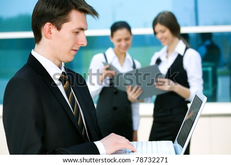 Young businessman and his pretty colleagues - stock photo