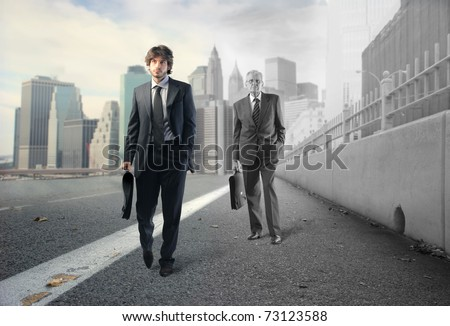 Young businessman and older businessman walking on a street
