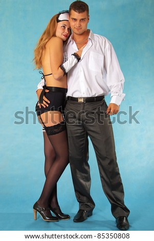 Young businessman and parlormaid in loving embrace on blue background