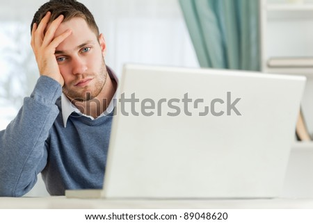 Young businessman annoyed by notebook in his home office