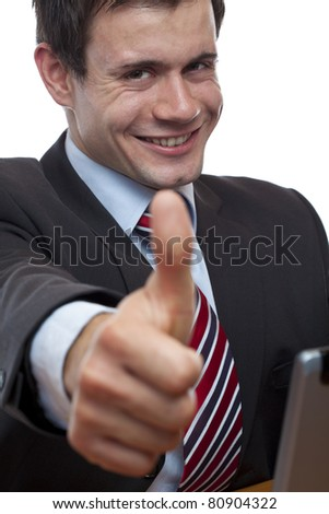 Young businessman at desk shows thumb up. Isolated on white background. - stock photo