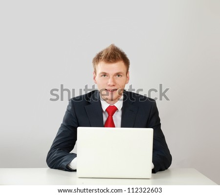 Young businessman at his workplace, isolated on white background