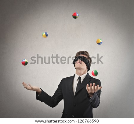 young businessman blindfolded playing with balls