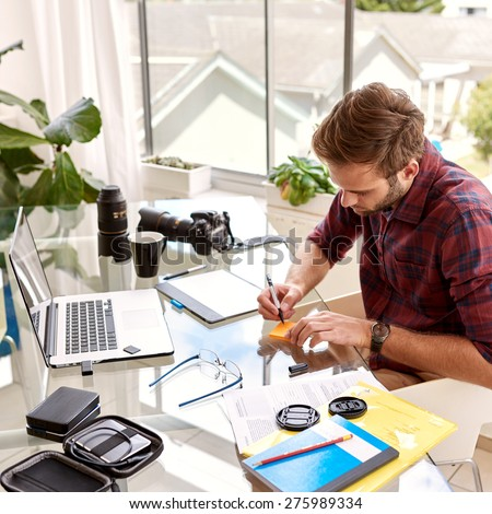 Young businessman busy taking notes on a note pad, sitting at his glass desk in his home office with his morning coffee