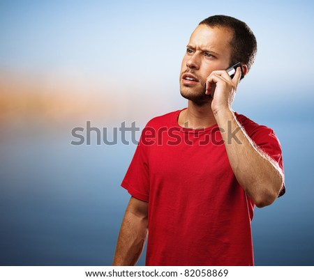 young businessman calling on mobile phone in the beach