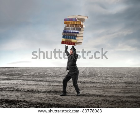Young businessman carrying a stack of books on his shoulders