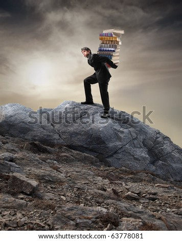 Young businessman carrying a stack of books while climbing a mountain