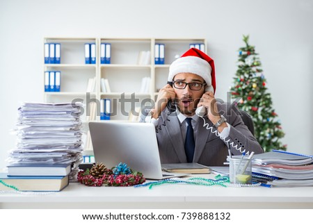 Young businessman celebrating christmas in the office #739888132