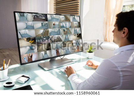 Young businessman checking CCTV camera footage on computer over desk in office #1158960061