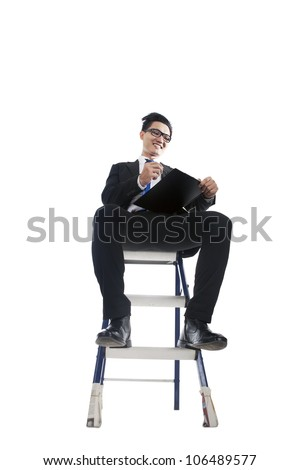 Young businessman checking list and sitting on ladder, isolated on white