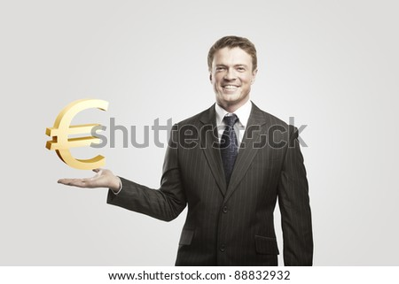 Young  businessman chooses a Gold Euro Sign.On a gray background