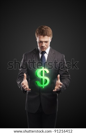 Young  businessman chooses a green US dollar sign. On a black background